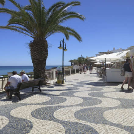 Seats, palm trees, market stalls near Luz Beach